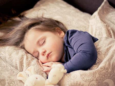Kleinkind schläft im Bett und träumt
