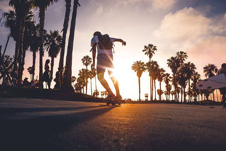 Skateboard fahren am Strand mit Palmen
